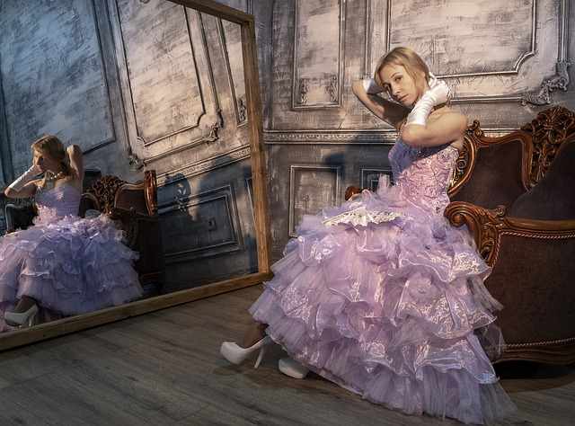 dívka, která sedí v plesových šatech v křesle